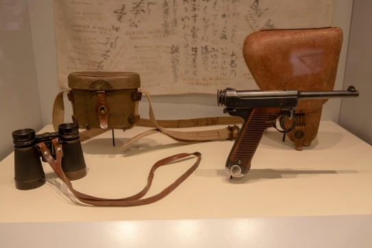 Japanese Flag with Signatures of U.S. Soldiers. Captured by a 41st Infantry Division soldier in the Pacific Theater, circa 1944 (LEW-00750), Japanese Army Field Binoculars and Case (LEW-13021 and LEW-13022), Japanese Semiautomatic Type 14 Pistol (LEW-11015), Japanese Army Pistol Holster (LEW-11776)