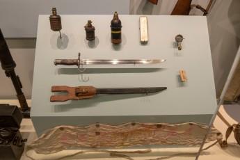 Japanese Fragmentation Grenades (LEW-06515 and LEW-11581), Japanese Mortar Round (LEW-00113), Japanese Army Syringe Kit circa 1942 (LEW-003034), Japanese Army Compass (LEW-00293), Japanese Army Wooden Identification Tag, circa 1942 (LEW-11404), Japanese Army Bayonet and Scabbard, circa 1939 (LEW-11777 and 11778), Japanese senninbari, sash (or belt) of 1,000 stitches (LEW-13344)