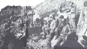 """Lt. Col. Rudder's Command Post was set in a cratered niche at the edge of the cliff. German artillery searched for it, but most of the enemy shells were """"overs"""" into the sea. Lt. Eikner, in charge of the communications section, is near the center, drinking from his canteen."""