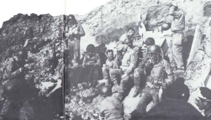 "Lt. Col. Rudder's Command Post was set in a cratered niche at the edge of the cliff. German artillery searched for it, but most of the enemy shells were ""overs"" into the sea. Lt. Eikner, in charge of the communications section, is near the center, drinking from his canteen."