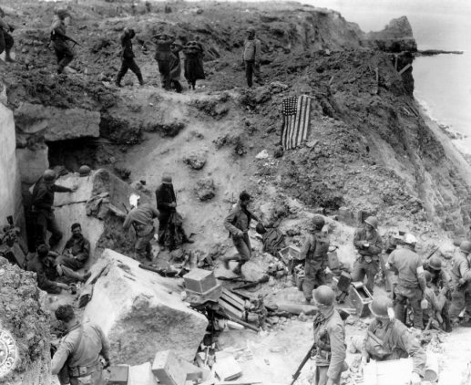 After relief on D+2, when American flag had been spread out to stop fire of friendly tanks coming from inland. Some German prisoners are being moved in after capture by the relieving forces.
